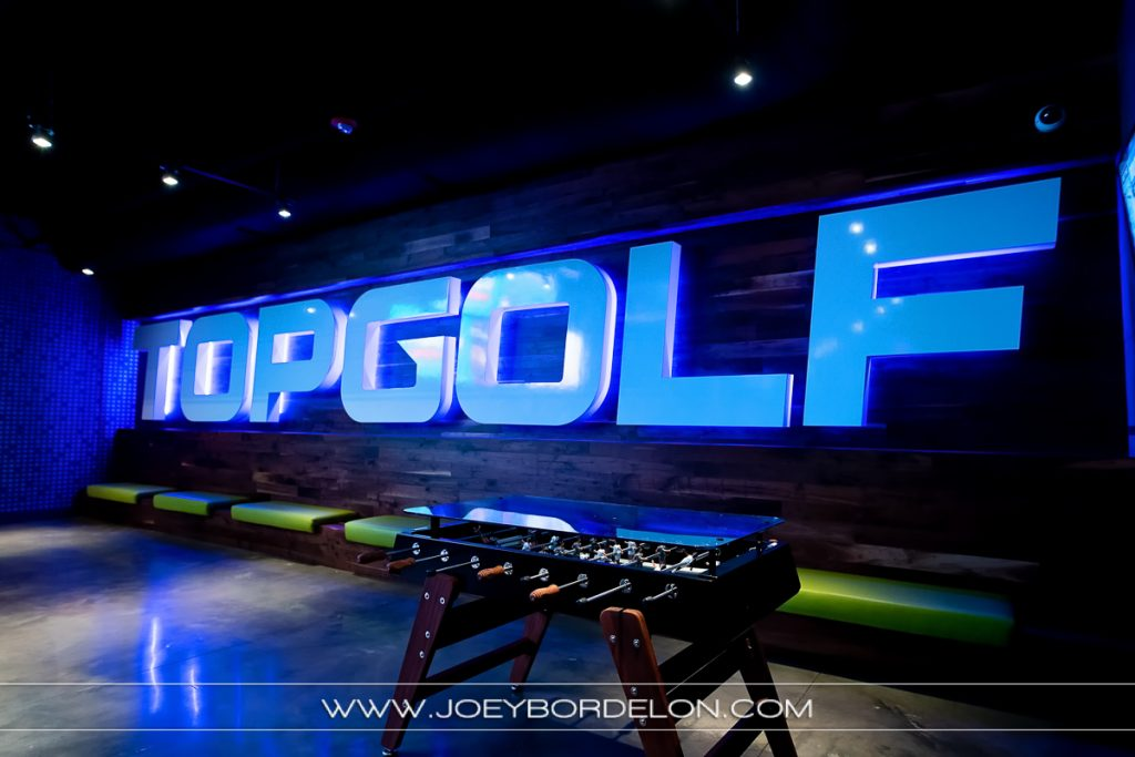 Top Golf Baton Rouge bar area's sign and game table